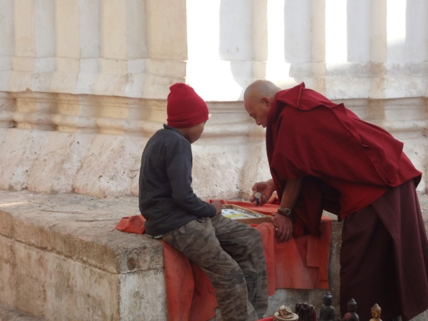 Nepal: Monk playing game with kid